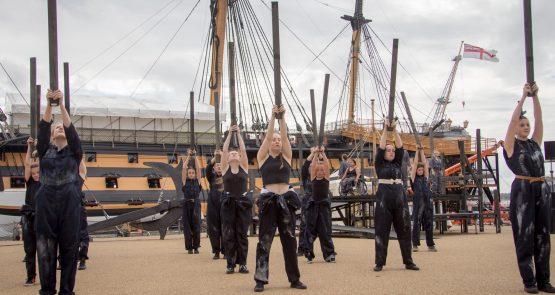 Group photo from a live outdor performance of the Seafarers - dancers hold wooden posts high above their heads.
