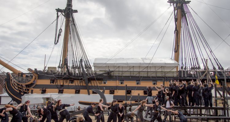Outdoor performance of The Seafarers - dancers against a backdrop of a large ship.