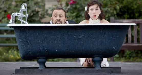 Lucy Bennett and Sir Dave Toole in Bill & Bobby - their faces visible over the rim of cast iron bath