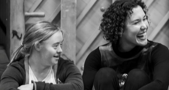 A black and white photo of Hannah Sampson and Amy Butler, they both look to their left, Amy has a big grin.