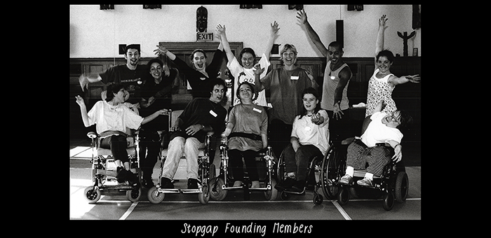 A black and white photo of an excited group posing for the camera. In white text along the bottom of the image is the title 'Stopgap Founding Members'.
