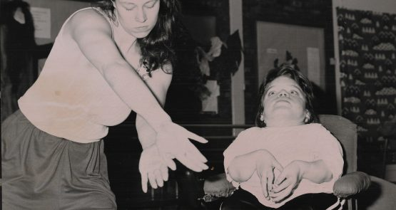 Black-and-white photo of Vicki Balaam dancing next to a wheelchair dancer.