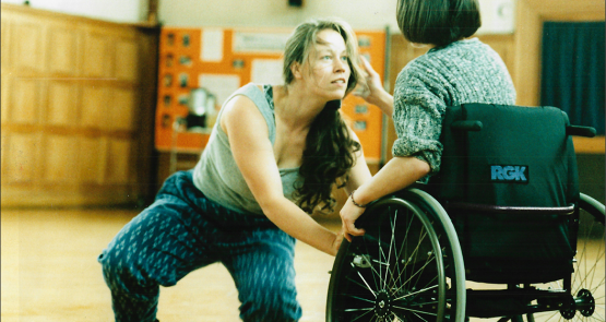A photo of Vicki Balaam in duet with a dancer in a wheelchair who has their back to the camera.