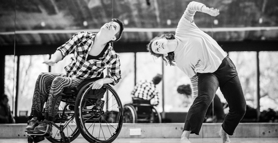 ID: Black-and-white photo of SG2 dancers Kat and Abi moving together in the studio. Kat is white, with short, dark hair. She is wearing a checkered shirt, floaty trousers with a psychedelic pattern and dark trainers. Sitting in her wheelchair, she is leaning to the left, looking up. Abi dances next to Kat on her left side. She is a white, standing dancers with shoulder-length, dark-blond hair. She is wearing a white, baggy t-shirt over a long-sleeved, striped top and dark trousers. She is barefoot. With her knees bent, she is leaning to the right, towards Kat, looking up, with her left arm mid-move upwards as well. Image by Chris Parkes.