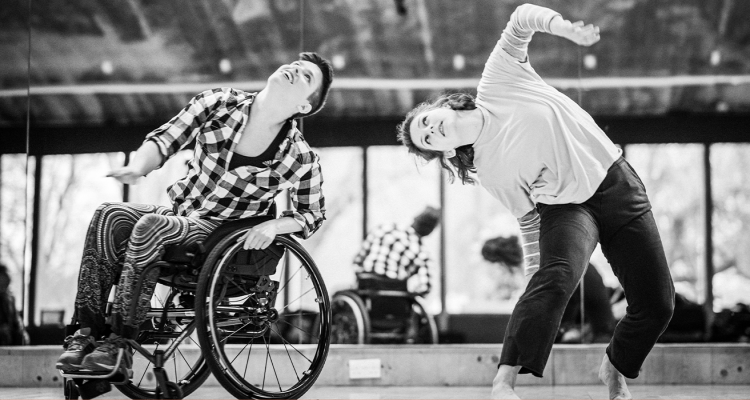 Black-and-white photo of SG2 dancers Kat and Abi moving together in the studio.