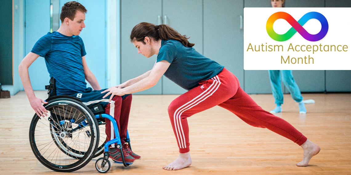 ID: A photograph of Fin and Sander dancing together, in the top right corner a rainbow infinity symbol with World Autism Acceptance Day in gold text. The photo captures Sander and Fin from the side, On the right; Fin a tall standing dancer lunges deeply forward, pressing his hands on Sander's knees. Sander, in their blue framed wheelchair, prepares a hand on the left wheel and focusses towards Fin. Sander is white with short dark blonde hair, they wear a blue shirt and red and blue joggers with a white stripe down the side. Fin is white, his long dark hair tied in a ponytail, he wears a blue top and bright red joggers with three white stripes down the side, he's barefoot. They dance in a blue walled studio, in the right top corner of the image hidden mostly underneath the overlaid symbol, Siobhan stands an observes them.