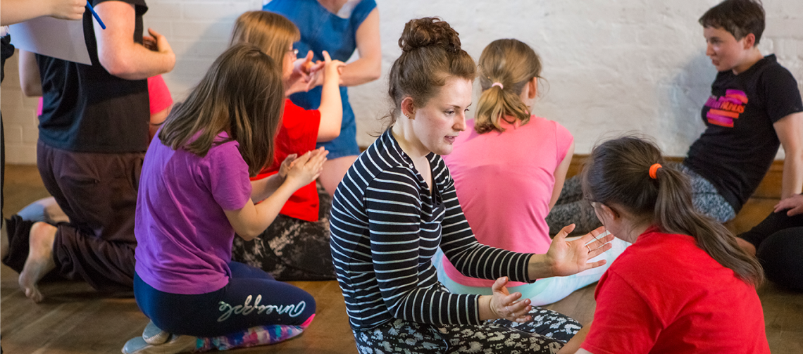 ID: An image of Lily surrounded by youth company dancers as they take part in a workshop. Lily kneels on the floor and holds their hands out in front whilst they work with another dancer. Lily is white, their coppery brown hair is tied up in a bun, they wear a striped top and patterned trousers.