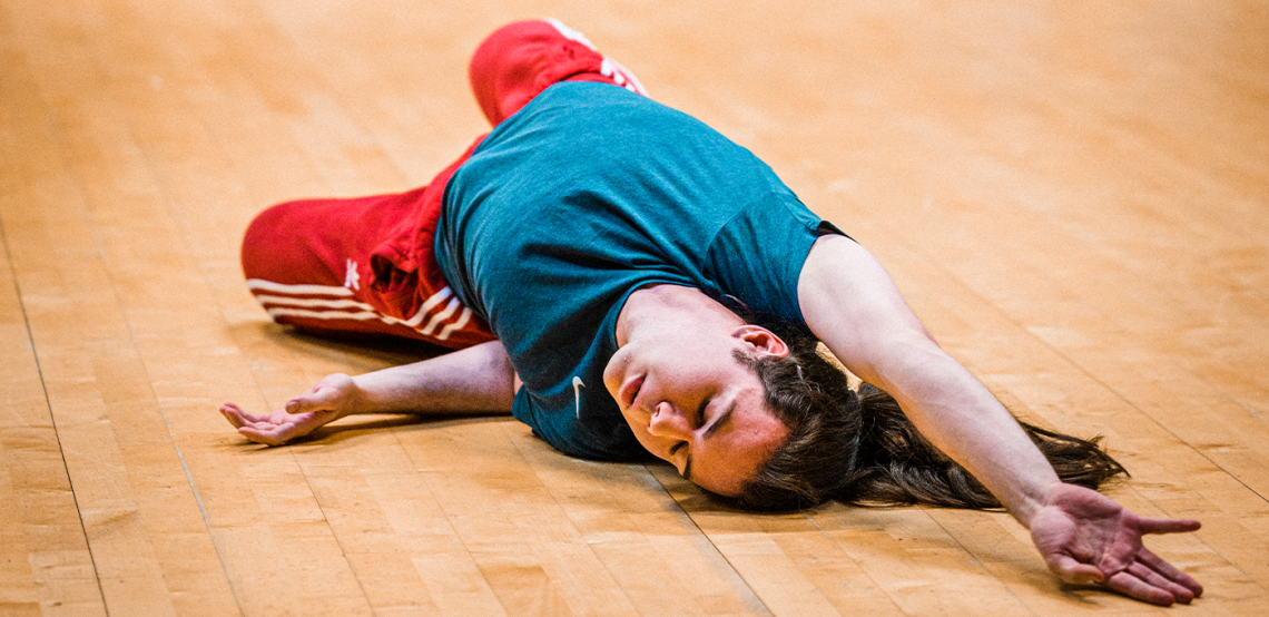 ID: A photo of Fin dancing on the floor, he lays down reaching an arm above his head, eyes closed.