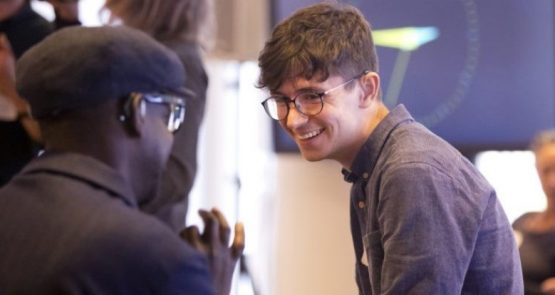 Photo of James in conversation with a person who has their back to us in the foreground of the image. James smiles as he focusses on the other person. James wears a hearing device, he is white and has short dark brown hair, he wears glasses and grey-blue shirt. The person in the foreground is Black, they wear a hearing device and glasses, have a black flat cap on and a black shirt.