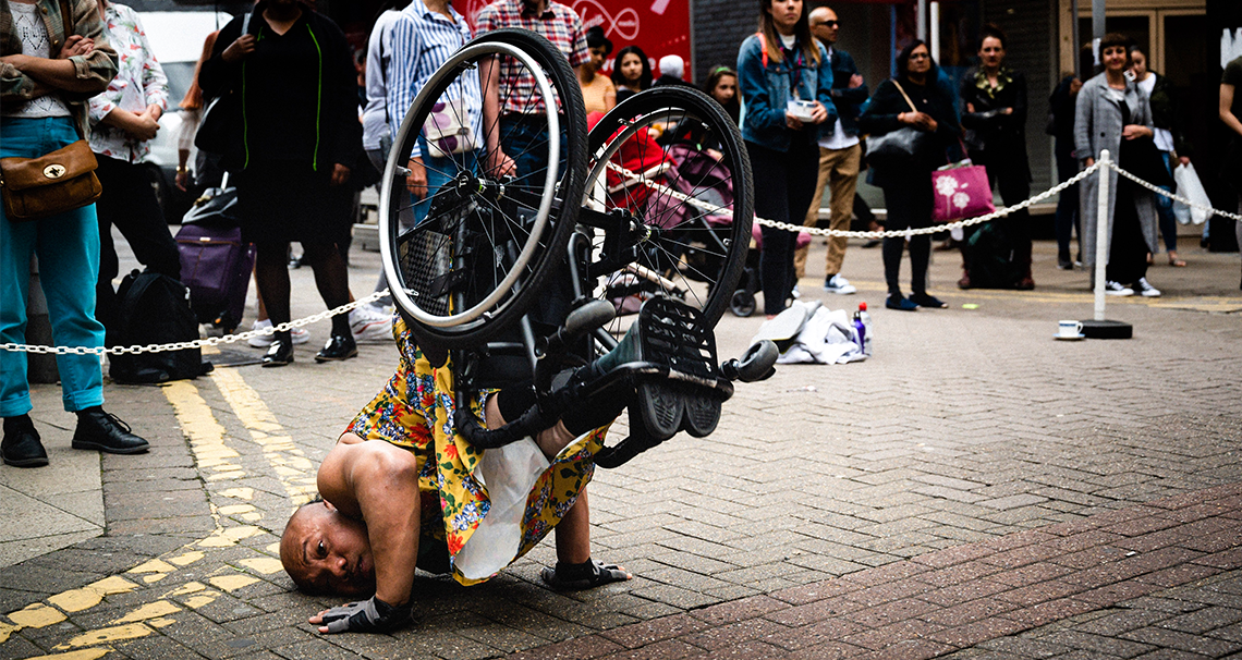 Nadenh balances in a shoulder stand in his wheelchair, his head pressed against the pavement and hands bracing himself as he lifts his lower body and lightweight black chair into the air.