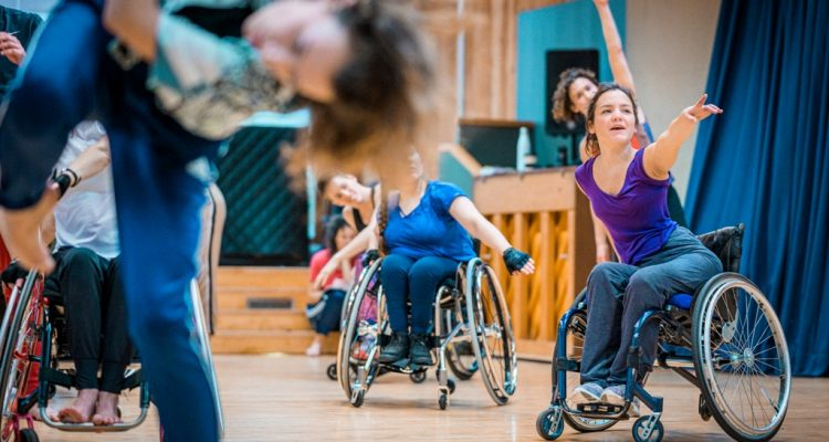 Laura Jones dancing in the studio in her wheelchair, surrounded by other company dancers. Photo: Chris Parkes