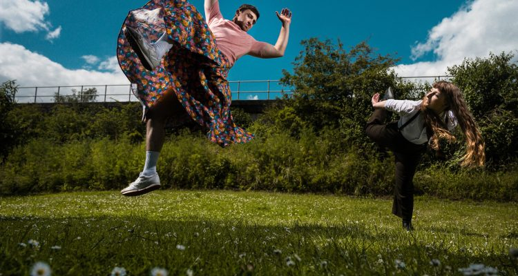 Alice and Christian dancing together on a grassy field, Christian leaps and Alice balances on one leg.