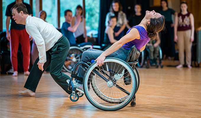 A photo of Laura travelling across a studio, other dancers surround the background of the image. Laura tips backwards in her wheelchair and looks upwards, she is suspended in a wheelie and balancing using her small tail wheel which attaches to the back of her chair. Laura is white, her dark brown hair tied in a bun, she wears a purple top, grey joggers and trainers.