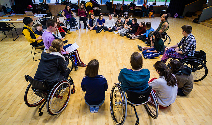 A photograph of the Stopgap team and associate artists, all in a big circle listening and talking to one another. They are in a brightly lit studio space, with wooden panelling, windows behind them open out to a green space. Some people are sat on the floor, others are in their wheelchairs, others sit on chairs.