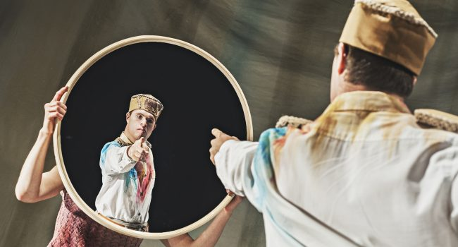Chris points accusatorily at himself in a circular mirror.