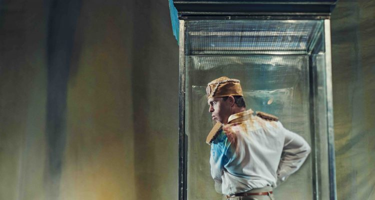 Chris Pavia stands within a clear vitrine, dressed as his dictator character in Artificial Things