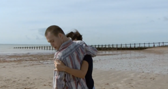 Chris and Lucy embrace on a beach.