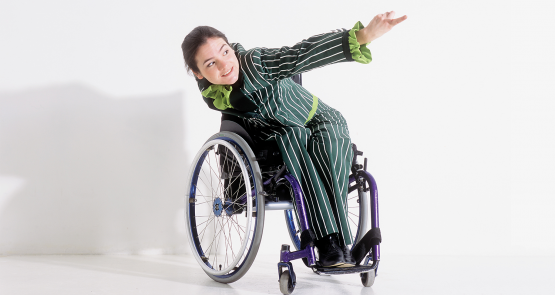 Laura, a wheelchair dancer, in a pinstripe green suit, leans forward and extends an arm.