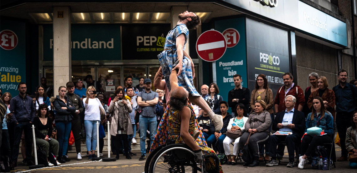 Three dancers during a Frock performance, seated and standing audience watch in front of a storefront on a high-street.