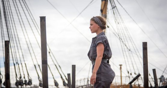 Siobhan during the Seafarers, she stands tall with ship masts and rigging in the background.