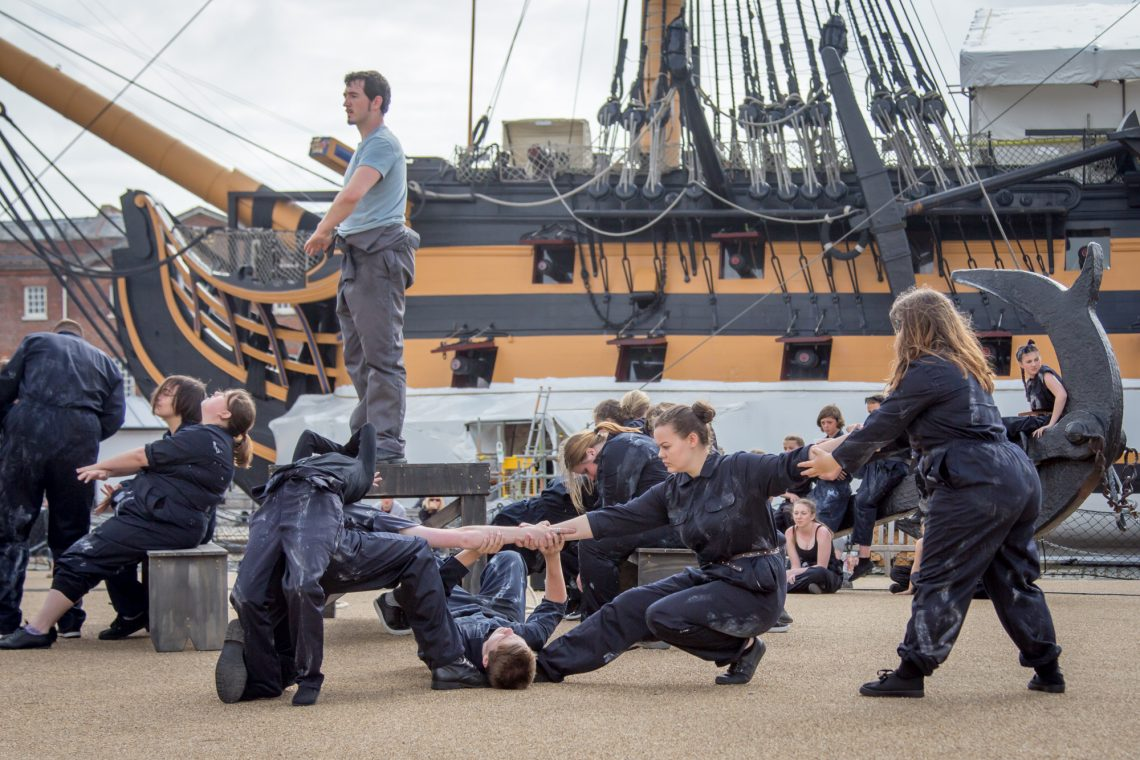 A group of dancers in dark blue overalls reach and pull against each other across the image. Set in front of a wooden ship in black and muddy orange paint.
