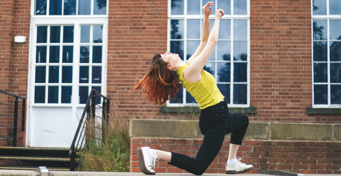 A photo of Lauren dancing outside against a red-brick building with large windows. Lauren lunges forward, her back knee touching concrete floor. She throws her head back, releasing her arms upwards and leaning back with the motion. Lauren is white, her long red tipped hair flows loose as she dances. Lauren is wearing black skinny jeans, a chartreuse yellow vest, and white trainers