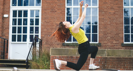 A photo of Lauren dancing outside against a red-brick building with large windows.