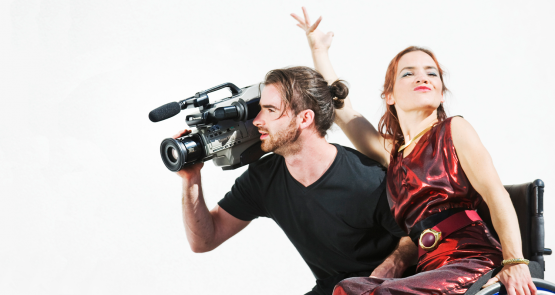 SPUN Productions. Two dancers side by side, one holds a big black film camera and looks through it, the other flamboyantly holds her hand up.