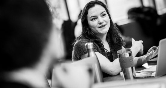 Black-and-white portrait of Laura Jones in conversation with other people sitting at a table. The others are blurred or out of shot so that the focus is solely on Laura.