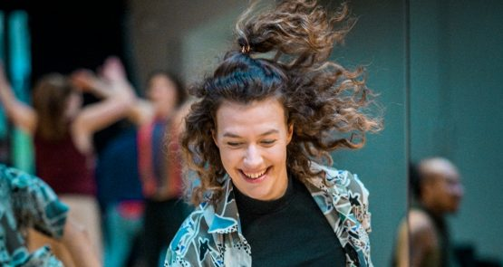 Portrait of Millie dancing in the studio, her long, brown, curly hair flying mid-movement. Millie is looking down, laughing.
