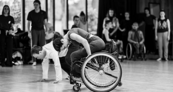 Black-and-white photo of Laura Jones dancing in her wheelchair in the studio. She is diving forward, gripping the wheels of her wheelchair. Chris Pavia is on all fours on the floor behind her, and in the background other dancers are watching.