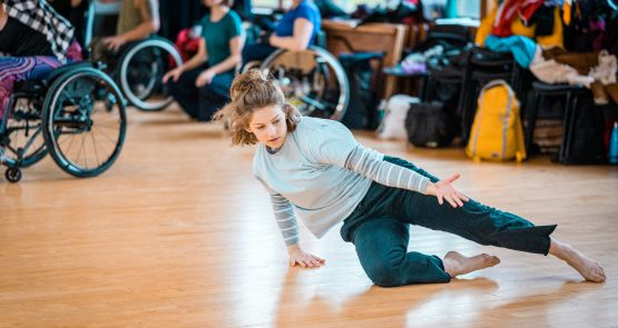 Abbie dancing on the floor of a dance studio, resting on her right hand and knee, with her left leg and arm outstreched. In the background, blurred, is a group of wheelchair dancers on the left and a pile of clothes and bags on the right.