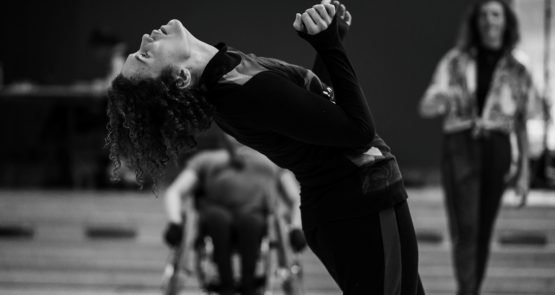 Black-and-white photo of Amy dancing in the studio. She is arching back, gaze lifted to the ceiling, whith her hands lifted up before her chest. Blurred in the background are a wheelchair dancer, framed by Amy's arched back, and a standing dancer.