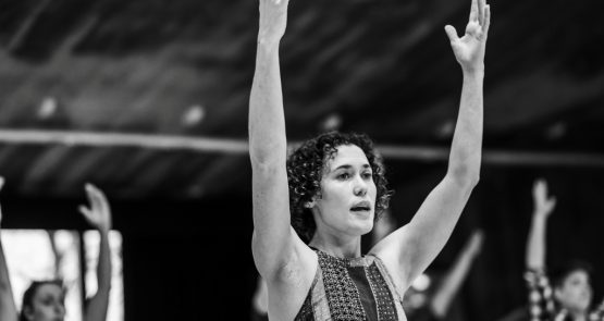 A black and white photo of Amy Butler leading class in a studio, she has both arms raised.