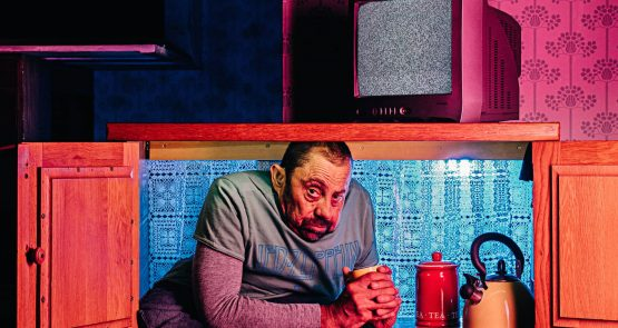 Dave Toole sits in a cupboard, pink and blue lights tint the image.