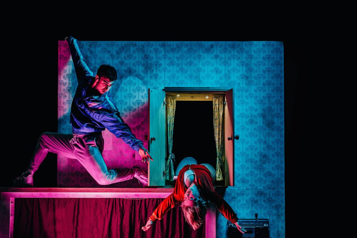 Photo from The Enormous Room - Christian reaches towards Hannah as she leans out from an open cupboard.