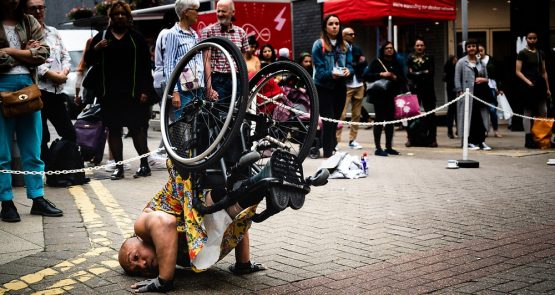 Photo of Nadenh, one of Stopgap's wheelchair dance artists during an outdoor performance of Frock. He balances in a shoulder stand in his wheelchair, his head pressed against the pavement and hands bracing himself as he lifts his lower body and chair into the air. He looks towards the front of the image and we see the underside of his chair. Nadenh is a brown-skinned Cambodian man, he wears a floral yellow dress, black fingerless workout gloves and black trainers. A crowd of people watches in the background.