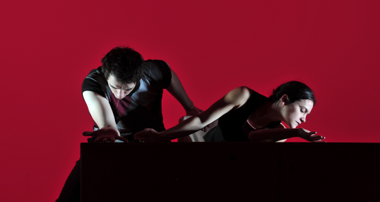 Two dancers at a table, one leans forward the other leans outward. With a deep red background.