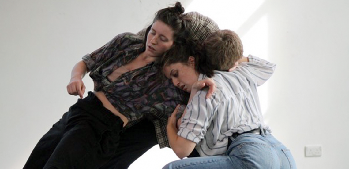 Three dancers entangled during a contact improvisation. One of the dancers is Lauren, she leans into the other two, their heads close and faces focussed whilst they tune in through their bodies.