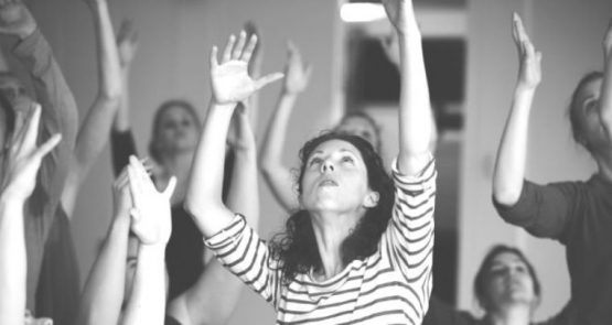 Black and white photo of Lucy among a group of dancers, lifting their arms up