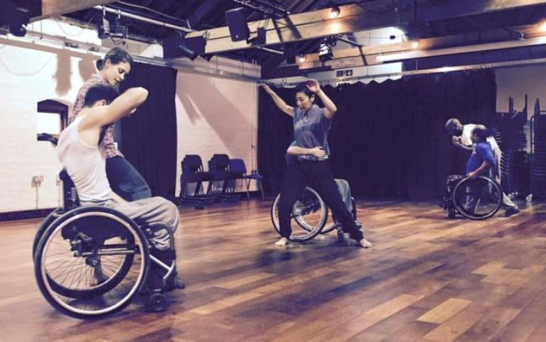 A group of 3 standing and 3 wheelchair dancers in a studio.