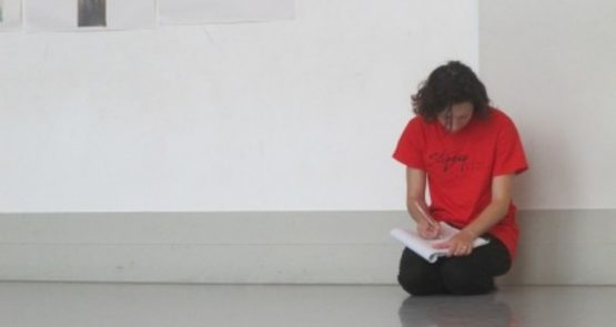 Photo of Lucy Bennett kneeling on the floor, writing into a notebook.