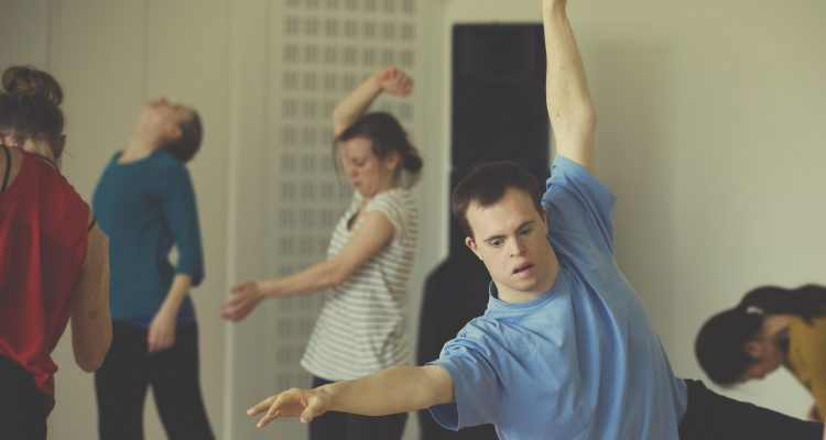 Photo of Chris Pavia dancing among other dancers in the studio