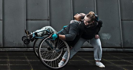 Nadenh and Hannah in The Awakening. Nadenh tips back on the main wheels of his wheelchair. Hannah is behind him, leaning forwards to take Nadenh's weight. His head rests on her shoulder.