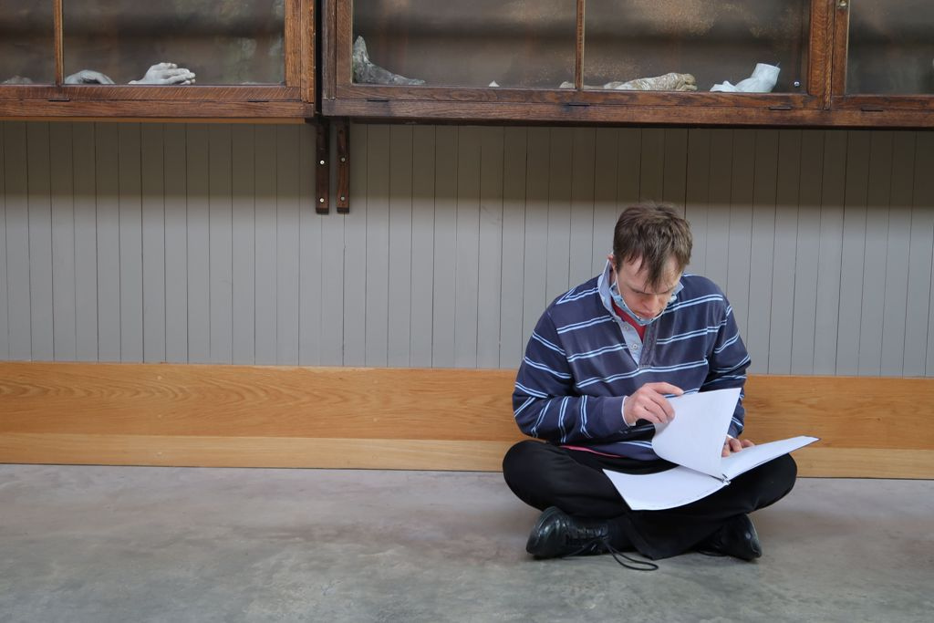Photo of Chris Pavia sitting cross-legged on the floor, looking through some notes.