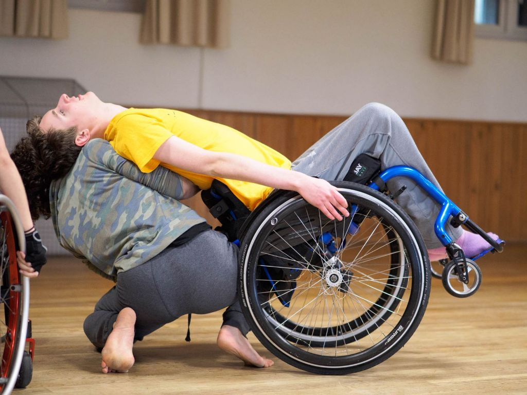 A photo of Sander dancing in the studio. He is sitting in his wheelchair, dressed in a yellow t-shirt, grey jogging trousers and socks. He is tipping far back on the wheels of his chair, resting his back and head on another dancer who is kneeling on the floor behind Sander, supporting him with their back to the camera. They have short, curly brown hair and are dressed in grey jogging trousers and a camouflage top.