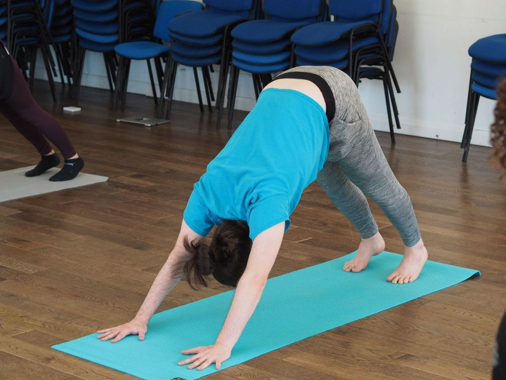 """A person in a turquoise t-shirt and grey jogging pants is performing the """"downward dog"""" pose on a turquoise yoga mat."""