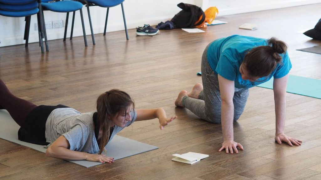 Two young women on the dark wooden floor of a studio. The one on the left is lying on her front on a grey yoga mat, arms bent at the elbows. She is lifting her head, rib cage and left arm off the mat. In front of her is an open notebook. The other is kneeling in the floor beside her. She is on all fours, also looking at the notebook.