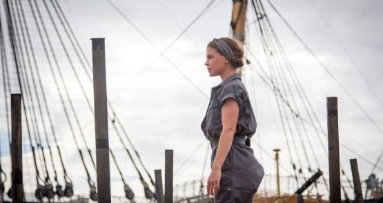 Siobhan in a performance of The Seafarers at Portsmouth, with the masts and rigging of the HMS Victory behind her.
