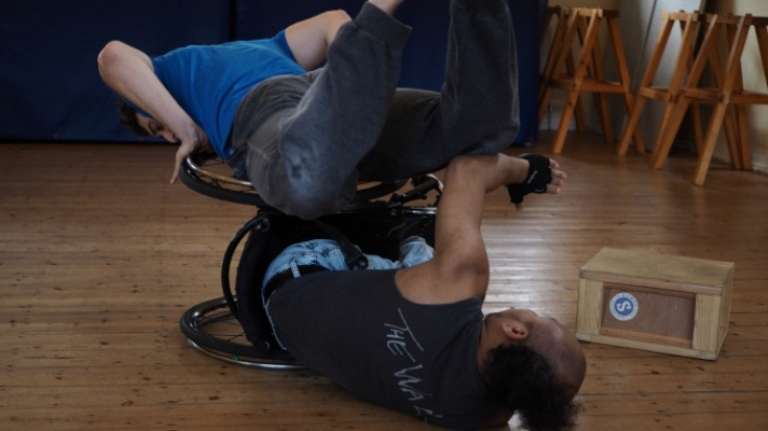 """Nadenh and Christian rehearsing a duet. Nadenh is lying on his side in his wheelchair, with his back to the camera, on the wooden floor of a dance studio. He is wearing a dark tank top with """"The Wall"""" written across its back, and light blue trousers. Also with his back to the camera, Christian is lying front-down on the top wheel of Nadenh's chair. His knees are bent, sending his feet up, parallel to the ceiling. He is pressing down on the wheel with both hands, looking down on the floor. He is wearing a blue t-shirt and dark trousers."""